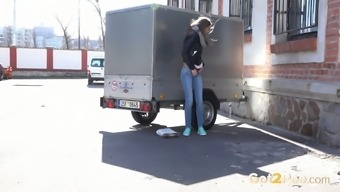 Skinny young hottie hides behind the trailer and pisses
