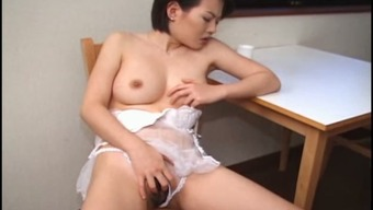 Voracious mom Kiyomi enjoys a working sex toy in her cunt
