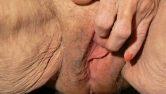 Old depraved woman is finger banging her pretty pink pussy